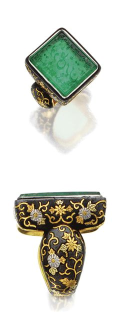 EMERALD INTAGLIO RING.  The rectangular emerald intaglio carved with an inscription borderd by decorative elements, measuring approximately 20.0 by 17.0 by 3.4 mm., within a silver and gold mounting engraved with flowers and scrolls, mounting probably Chinese, 19th Century