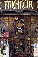 Farmacia Enrich, situada en la calle Muntaner nº 83, fue fundada en el año 1902. En la puerta de acceso, el hierro es el elemento básico que enmarca geométricamente las diferentes vidrieras. En la parte superior destaca la decoración de guirnaldas y las líneas onduladas, en contraste con las líneas rectas de todo el paramento vidriado central, y en la parte inferior aparece de nuevo el zócalo ondulado de hierro, característico del modernismo. Barcelona