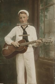 Les Paul, ca. 1920-1929, Waukesha, Wisconsin ..  Portrait of Les Paul wearing a sailor outfit. Paul poses with his acoustic guitar and harmonica. Lester Polfuss, better known as Les Paul, is best known for creating the solid body electric guitar.