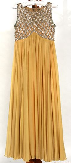 1960S VINTAGE EVENING GOWN. Early 1960s vintage evening gown, sleeveless, Empire waist, bodice nude mesh with crystal bead and sequin diamond pattern, gathered mustard yellow silk chiffon hangs from bodice in flowing manner to floor, zip back, hook and eye closures on bodice. Tag: Vendome Kaufmann's Eleventh.