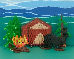 Have fun creating this wilderness camping scene in Perler Beads, complete with a tent, campfire, pine trees, and a mama and baby bear!