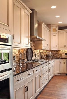 light cabinets, dark counter, oak floors, neutral tile black splash.