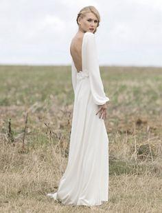 Novia con vestido vaporoso de manga larga y escote en la espalga. #Blog #Innovias #Vestidosmangalarga