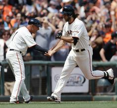 San Francisco Giants' Madison Bumgarner, right, is congratulated by third base coach Tim Flannery after hitting a grand slam off Arizona Diamondbacks' Matt Stites during the sixth inning of a baseball game Sunday, July 13, 2014, in San Francisco. (AP Photo/Ben Margot)