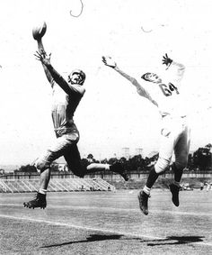 Photo Title  Pass Play  Photographer/Creator  Dick Turner  Collection  1950  Publisher  ACME Newspictures  Caption/Description  Photo shows U.C.L.A. end Ernie Stockert (50) snagging a pass during intra-squad game. Milton Davis, Left Half, (64) jumps in futile effort to break up play.