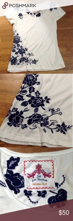 """Johnny Was white/navy embroidered short sleeve top This Johnny Was white/navy embroidered short sleeve top is in great condition, with no holes or stains.   Navy embroidered flowers on the front and back.   Size tag was removed by previous Posher, but would probably fit a larger small or medium.  Measurements:  Pit to pit: 17"""" Length: @ 19.5""""  Great with your favorite skinny jeans and bomber jacket this fall. Johnny Was Tops Tees - Short Sleeve"""