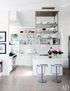 In the kitchen, specially crafted steel shelves are suspended above the island and a pair of barstools from Design Within Reach | archdigest.com