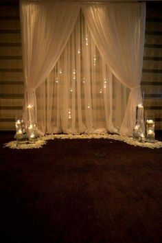 Sheer fabric backdrop with cylinder vases and rose pedals