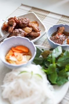 Ha Noi grilled pork meat served with warm fish sauce, rice noodle, fresh herb leaves.