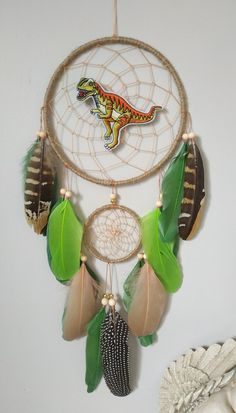 Cute dinosaur room decor dream catcher fun gift idea Beautifully crafted one of a kind dreamcatchers! Perfect for: home decor, nurseries, children's bedrooms, birthdays, parties, photo props, and much more! Makes a thoughtful gift for a Loved one or yourself. Measurements: Dreamcatcher ring 6 inches across 18 inches from the top of the ring to bottom of feathers ( not including cotton hanger) Nursery Decor Boy, Woodland Nursery Decor, Boys Room Decor, Dream Catcher Decor, Large Dream Catcher, Cute Dinosaur, Dinosaur Birthday, Dinosaur Room Decor, Gold Wall Decor