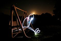 Man made from light sitting on swing