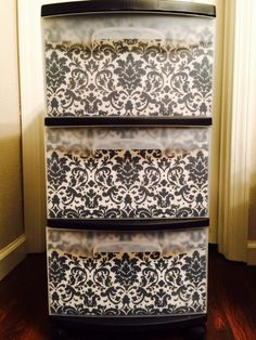 Plastic storage cart makeover: damask fabric covered cardboard pieces cut to fit the inside of the drawers--removable so the design can be changed anytime