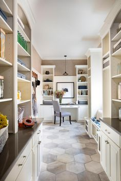 A stunning blue and white tiled backsplash and floor-to-ceiling cabinets combined with a grandiose island for entertaining anchors this family-friendly kitchen.