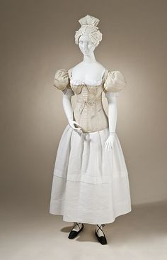 Pair of woman's sleeve plumpers, England, 1830-1835. Linen plain weave with down fill. Corset, Europe, 1830-1840.quilted cotton sateen. Chemise, Europe, 1835, linen. Petticoat, Europe, 1830-1835, cotton. Shoes, France, c. 1835, silk satin and leather.