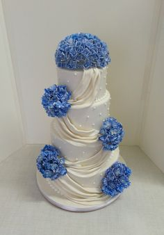 https://flic.kr/p/yBuktT | Four tier white wedding cake with fondant drapes and blue gum paste flowers. | Design was send in by client. Flowers made by Delia Mostert
