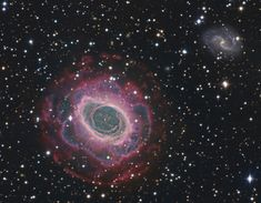 M57 Ring Nebula Deep Field. M57 is a planetary nebula some 2000 ly away in the constellation Lyra. The central ring is about one light-year across, but this remarkably deep exposure - a collaborative effort combining data from three different telescopes - explores the looping filaments of glowing gas extending much further from the nebula's central star.
