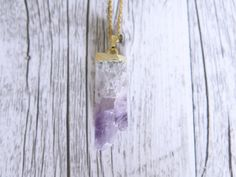 This beautiful necklace features a stunning raw piece of amethyst dipped in gold and suspended from a gold plated 18/45cm chain.  Amethyst is