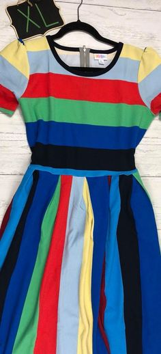 It's no secret that the LulaRoe Amelia dress is one of our most favorite LulaRoe styles! This one is black, blue, red, green, grey, and yellow striped! Check out our inventory, and shop in the comfort of your own home, in your pajamas! Visit our VIP shopping group here! www.bobbiesdreamers.com Carly · Sarah · Jill · Joy · Amelia · Lindsay · Shirley · Lynnae · Cassie · Madison · Julia · Randy · Lucy · Disney · Azure ·Nicole · Maxi · Lola · Irma · Classic T · Perfect T · Gigi