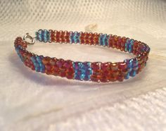 Beaded bracelet - blue and red pattern - handmade from quality Japanese seed beads. Includes cream organza gift bag. on Etsy, $14.95 AUD