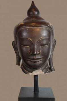 Head of Buddha  17th century     brown lacquered sandstone   H 38 cm   A refined representation and great meditative intensity qualify this Buddha head sculpted in sandstone.The decorative touch is added by a thick layer of brown lacquer. The hieratic face, toppeed by a ushnisha in the shape of a lotus flower bud, is typical for the Ava style in its square shape, the firmly drawn nose and the clearly marked eyebrows.