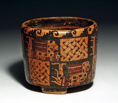 Pre-Columbian, Honduras, Ulua Valley, ca 550 to 900 CE. Polychrome pottery cylinder on three nubbin feet painted in shades of red, orange and black. With upper raised band with repeating series of human-headed glyphs painted upside down. Lower section painted with two panels showing a very elaborately decorated lord or god with fantastic headdress, arm extended as if giving an offering to the Mayan gods. Between each figure is a solid red panel framed in black and orange, and series of…