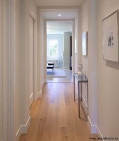 Crea un #pasillo luminoso con #suelos de madera y paredes blancas. #homedesigne #decoracion #diseño #hogar