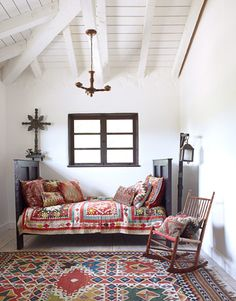 A Suzani quilt and kilim pillows give the guest room's Spanish Colonial-style daybed a dose of global pizzazz. The lantern is an early California cowboy lamp.