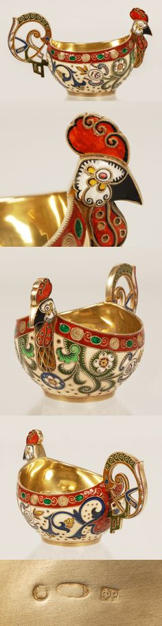 A Faberge silver gilt and shaded cloisonne enamel kovsh, workmaster Feodor Ruckert, Moscow, 1908-1917. The raised prow shaped as a rooster's head, the pierced upswept handle shaped as a stylized rooster's tail, the body enameled with stylized scrolling flowers on a cream ground. The rim is bordered of wire colis and translucent green lozinges on a red ground.