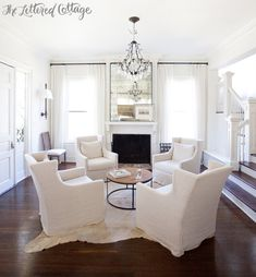 Neutral Living Room | White | Slipcovers | Cowhide Rug | Wall Sconces | Fireplace | Round Coffee Table | Ashley Gilbreath Interiors
