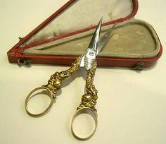 Horn of abundance scissors  In its red morocco leather box covered with golden grain trim, a silver gilt and polite steels scissors.  France, Circa 1825