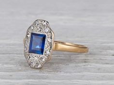 Antique Edwardian ring made in 18k yellow gold and platinum. Centered with an approximate .75 carat step cut sapphire and accented with single cut diamonds. Circa 1905 Edwardian ring sweet for an unusual engagement ring or stunning as a cocktail ring. Step cuts are in the same family as asscher and emerald cuts. They feature a hall of mirrors like effect. The step cut faceting of the blue sapphire enriches the color and over all effect of the stone. Diamond and gold mining has caused…