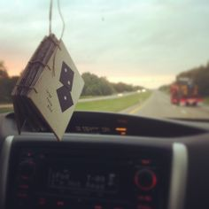 """A handmade book hangs in a rearview mirror, filled with amazing lyrics from the best songs about driving. In ode to the Cake song lyric, the book is called """"large fuzzy dice."""" Book by @linenlaidfelt as part of #myusedbook campaign."""