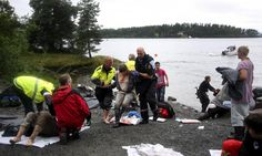 """""""A wounded woman is brought ashore opposite Utaoya island (in the distance) after being rescued from a gunman who went on a killing rampage targeting participants in a Norwegian Labour Party youth organisation event on the island, some 40 km southwest of Oslo, on July 22 , 2011."""""""