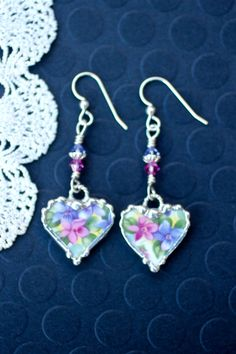 These charming earrings were made from Royal Albert, Nell Gwynne Series Richmond, broken chintz china and recycled into earrings. These earrings are a beautiful pink and purple floral china. They were decoratively soldered with a lead free silver alloy and hang from a sterling silver twisted jump rings and fish hook ear wires. They were wire wrapped with sterling silver wire. They are adorned with pink and purple Swarovski crystals and a sterling silver bead caps. The earrings dangle 1…