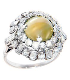 Cats Eye Diamond Platinum Ring,  Platinum and Diamond Ring set with Round and Baguette Diamonds totaling 1.50 Carats and centrally set with a 3.30 Carat Chrysoberyl Cats eye of Fine Honey Color with a very pronounced Eye. Circa 1960s