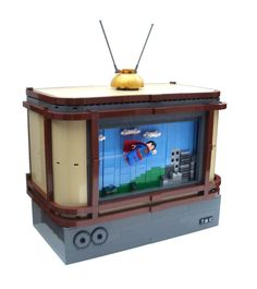 The TV features a scrolling backdrop which makes the Man of Steel soar through the skies over Metropolis. A video of the TV in action is attached below... The backdrop is built of alternating 1- and 2-brick width columns, mounted on a loop of bulldozer treads which allows it to scroll.