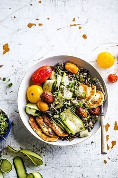 A fresh lentil salad topped with fried halloumi, roasted tomatoes and zucchini.