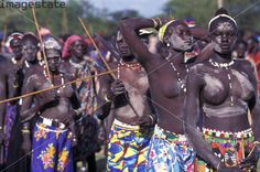 Spectators at a fattening up contest for men of the Dinka tribe who compete to see who is the fattest in the hope of finding a bride from among the unmarried women who believe that a fat man must be rich. Location: PAYIR, SUDAN