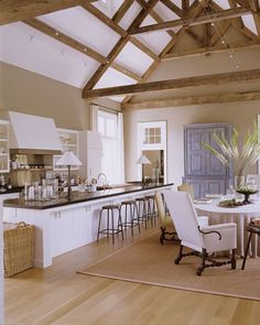 Rough-hewn salvaged beams lend dimension and warmth to kitchen-dining area. Axel Vervoordt cabinets anchor one wall and a huge Vervoordt basket at the end of the 18-foot-long counter holds all Ina's bakeware.