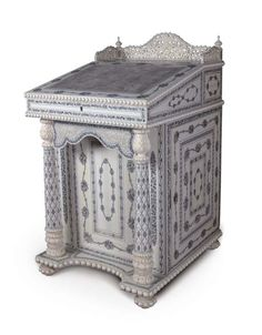 AN EXTREMELY RARE ANGLO-INDIAN IVORY AND PENWORK DAVENPORT DESK  SIGNED 'YENDAPILLY VERASALINGUM', VIZAGAPATAM CIRCA 1860-80  Inlaid and carved overal with scrolling foliage, with pierced scrolled three-quarter gallery above a hinged slope lined with grey velvet, enclosing a fitted interior above two shelves and three small drawers on one side, with columns framing the front panel, on a plinth mounted with balls, on conforming bun feet, the interior with dedication plate 'Prepared at the…