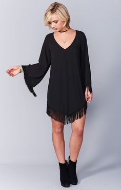 Yehaaaa for this dress! She is V neck with tassled long sleeves. The border of her dress has tassles to match her cowgirl sleeves and an attitude to rule the line dance.   *MADE IN THE GORGE USA* *100% Poly  *Lined in body, sheer in sleeves *Fringe detail on sleeves and hemline *Shell button closure in back  *Basically Wrinkle-proof.  Throw in purse for later recommended