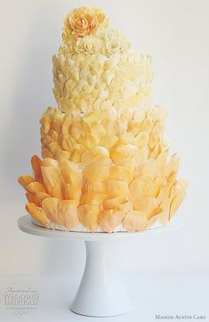 Unique looking cake covered in shades of orange petals.
