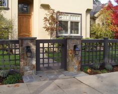 One of my favorites. I love the square pattern on the fence. This is unique. I like the matte black/gray finish. Love the stone columns with the lanterns. Love the stone pathway as well.