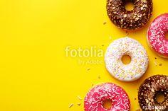 """Baixe a foto royalty free """"Flat lay donuts on a yellow background with copy space. Top view"""" criada por virtustudio com o menor preço no Fotolia.com.  Navegue no nosso banco de imagens online barato e encontre fotos stock perfeitas para seus projetos de marketing!"""