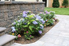 Highlight your landscape this spring with the help of Cambridge Pavingstones and Wallstones with ArmorTec. Cambridge Wallstones are perfect to highlight landscaping. Cambridge Pavers, Paving Stones, Wall Installation, Landscape Walls, Wall Colors, Backyard Landscaping, The Help, Outdoor Living, Plants