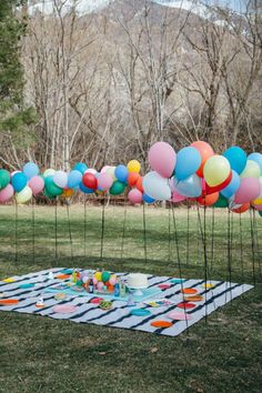picnic blanket surrounded by colorful balloons