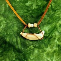 """Here I have put together all natural materials and woven them into this simple yet beautiful presentation with authentic carved bone beads and a copper wire wrapped tooth. This pendant is approximately 1 1/4"""" X 2"""" and is hung on an approximately 30"""" piece of brown leather lace. I made this one ex..."""