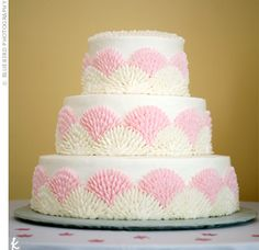 The three-tiered buttercream cake had textured zinnias in pale pink and ivory frosting.