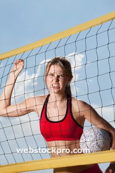 woman with beach volleyball clenching teeth