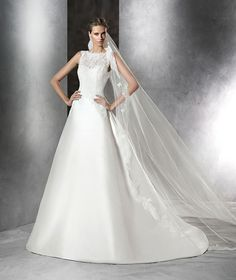 The New Design A-line wedding dress in mikado silk. Bodice with bateau neckline with sheer underbodice and sweetheart neckline with lace and gemstones. Plunging back. Frilly mikado silk skirt with gathers at the back of the waist.  Free Measurement